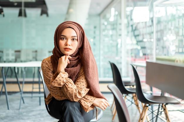 Młoda azjatykcia muzułmańska biznesowa kobieta w brown hijab przypadkowej odzieży obsiadaniu w kreatywnie kawiarni. Premium Zdjęcia