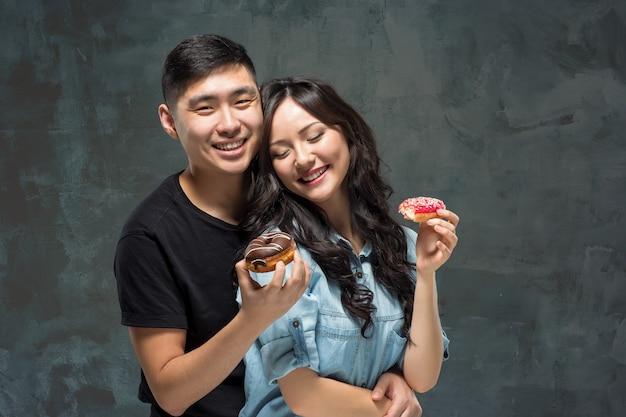 Młoda Azjatykcia Para Cieszy Się Jedzenie Słodki Kolorowy Pączek Darmowe Zdjęcia
