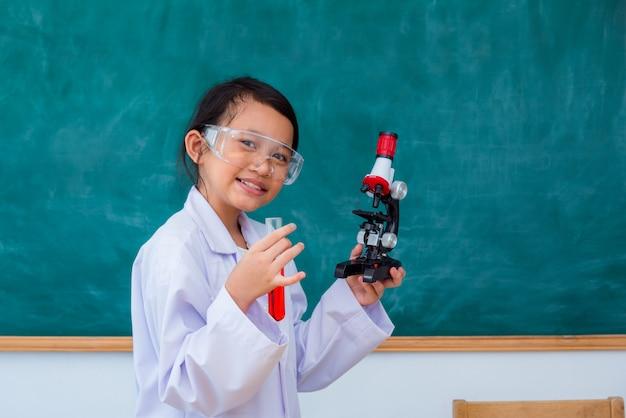 Młoda azjatykcia studencka pozycja i uśmiech w nauki sala lekcyjnej Premium Zdjęcia