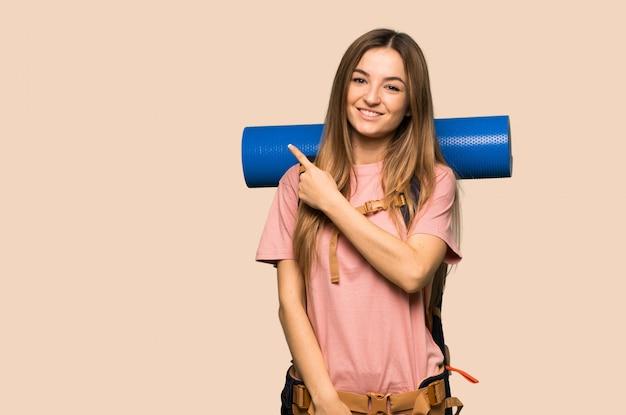 Młoda backpacker kobieta wskazuje strona przedstawiać produkt na odosobnionej kolor żółty ścianie Premium Zdjęcia