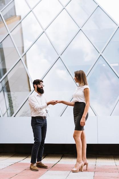 Młoda Biznesmena Chwiania Ręka Z Bizneswomanem Przed Nowożytnym Budynkiem Darmowe Zdjęcia