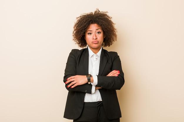 Młoda biznesowa amerykanin afrykańskiego pochodzenia kobieta nieszczęśliwa patrzeje w kamerze z sarkastycznym wyrażeniem. Premium Zdjęcia