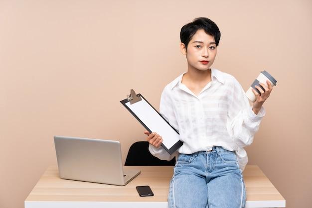 Młoda Biznesowa Azjatycka Kobieta W Jej Miejscu Pracy Premium Zdjęcia