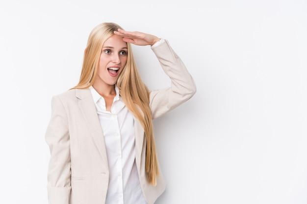 Młoda Biznesowa Blondynki Kobieta Patrzeje Daleki Utrzymuje Rękę Na Czole Na Białym Tle. Premium Zdjęcia