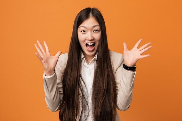 Młoda Biznesowa Chińska Kobieta świętuje Zwycięstwo Lub Sukces Premium Zdjęcia