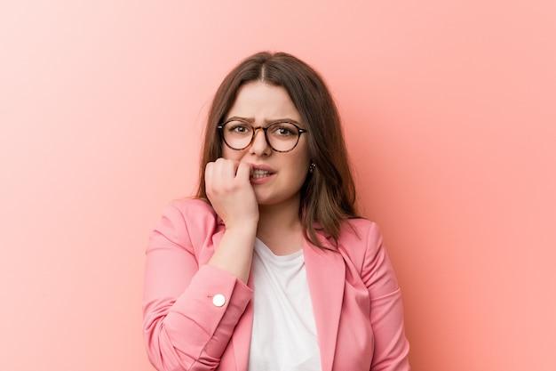 Młoda biznesowa kaukaska kobieta plus size obgryzająca paznokcie, nerwowa i bardzo niespokojna. Premium Zdjęcia