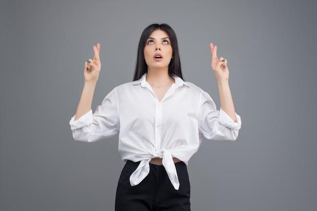Młoda biznesowa kobieta modli się i ma nadzieję na szczęście z kciuki Premium Zdjęcia