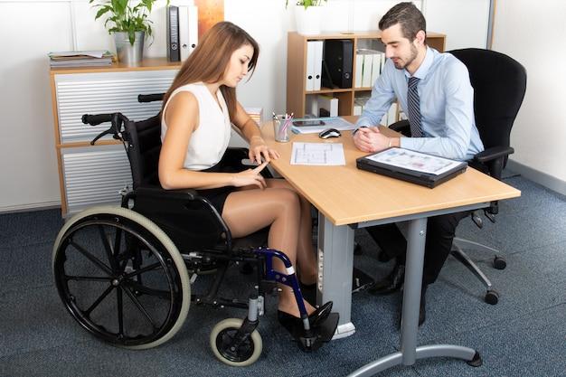 Młoda biznesowa kobieta na wózku inwalidzkim pracuje z męskim kolegą przy biurem Premium Zdjęcia