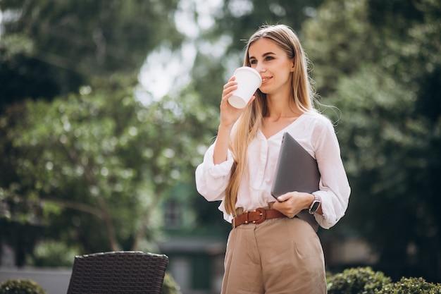 Młoda biznesowa kobieta pije kawę na zewnątrz kawiarni z laptopem Darmowe Zdjęcia