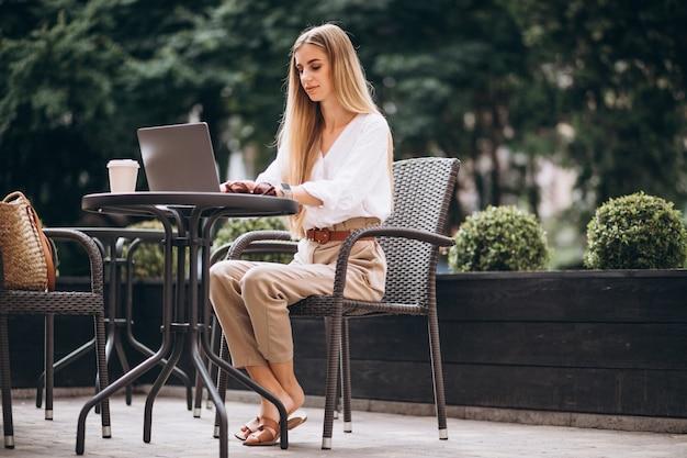 Młoda biznesowa kobieta pracuje na laptopie outside w kawiarni Darmowe Zdjęcia