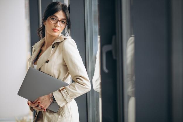 Młoda Biznesowa Kobieta Z Laptop Pozycją Okno W Biurze Darmowe Zdjęcia