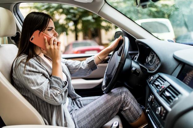Młoda Biznesowa Kobieta Za Pomocą Swojego Telefonu Podczas Prowadzenia Samochodu Darmowe Zdjęcia