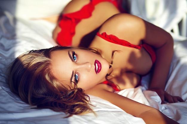 Młoda Blond Kobieta Jest Ubranym Czerwoną Bieliznę Na łóżku W Ranku Darmowe Zdjęcia