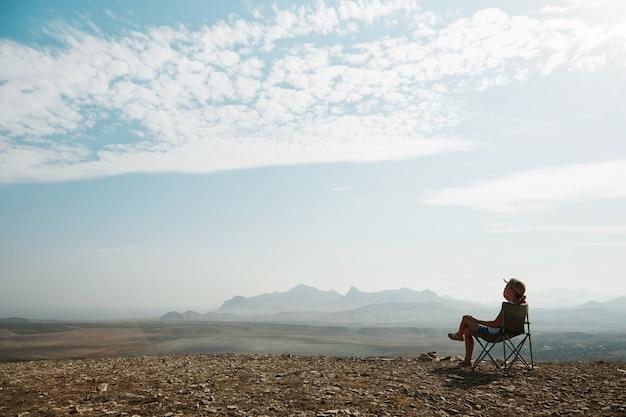 Młoda Blond Kobieta Siedzi Na Szczycie Wzgórza Darmowe Zdjęcia