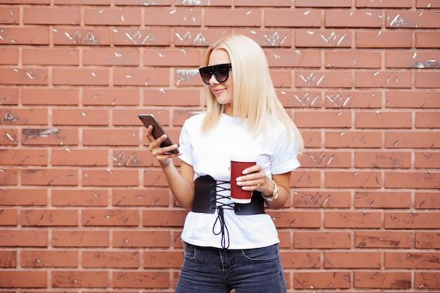 Młoda Blond Kobieta Stojąca Na Ulicy Picia Kawy Na Wynos I Korzystania Z Telefonu Komórkowego Darmowe Zdjęcia