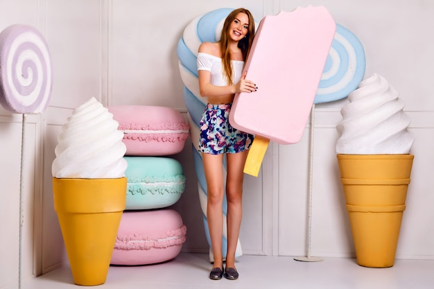 Młoda Blond śmieszna Kobieta Pozuje W Studio W Pobliżu Gigantycznej Słodyczy, Trzymając Duże Lody, Makaroniki, Sklep Ze Słodyczami, Stylowe Letnie Ubrania Darmowe Zdjęcia