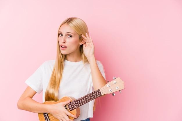 Młoda Blondynka Gra Na Ukelele, Próbując Słuchać Plotek. Premium Zdjęcia