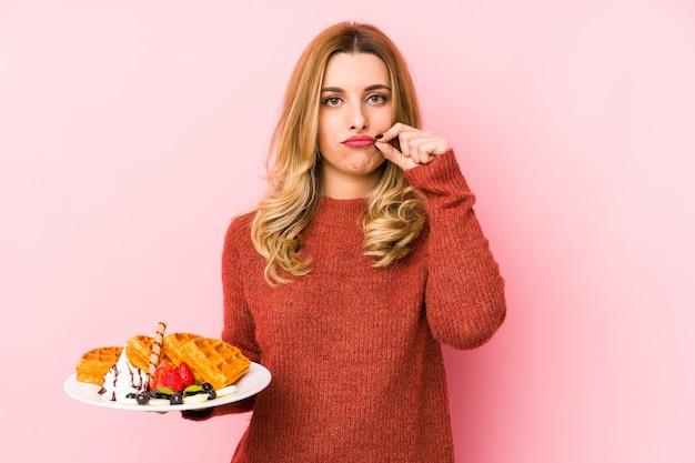 Młoda Blondynka Jedzenie Deser Wafel Na Białym Tle Z Palcami Na Ustach, Zachowując Tajemnicę. Premium Zdjęcia