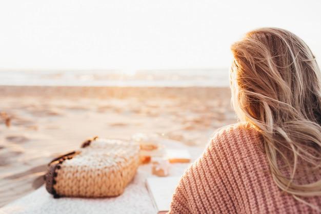 Młoda Blondynka Leżąc Samotnie Na Plaży Lub Oceanie I Patrzeć Na Horyzont. Kobieta Ubrana W Ciepły Sweter. Stonowanych Twarz Nie Jest Widoczna. Premium Zdjęcia