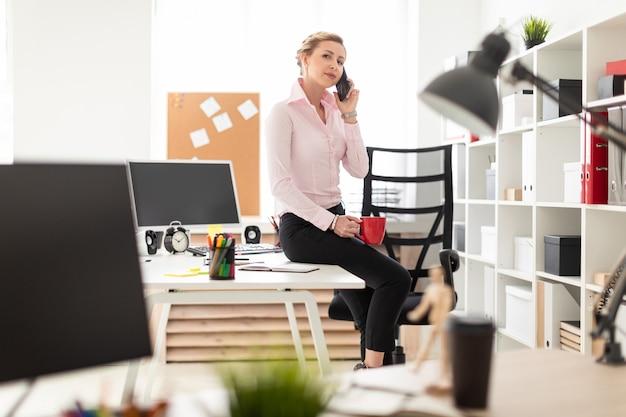 Młoda blondynka siedzi na stole w biurze, trzyma w dłoni czerwony kubek i dzwoni. Premium Zdjęcia