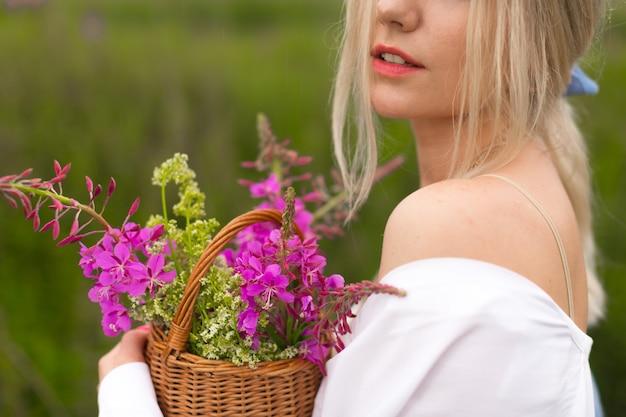 Młoda Blondynka Spacery Po Okolicy Trzymając Kosz Z Dzikimi Różowymi Kwiatami Premium Zdjęcia