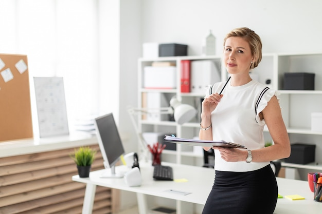 Młoda Blondynka Stoi Przy Stole W Biurze I Trzyma W Rękach Dokumenty Oraz Ołówek. Premium Zdjęcia