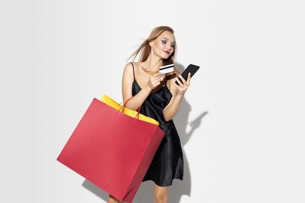 Młoda Blondynka W Czarnej Sukni Zakupy Na Białej ścianie Darmowe Zdjęcia