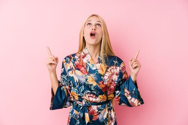 Młoda Blondynka W Piżamie Kimono Skierowaną Do Góry Z Otwartymi Ustami. Premium Zdjęcia