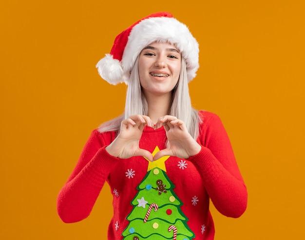 Młoda Blondynka W świątecznym Swetrze I Santa Hat Patrząc Na Kamery Z Uśmiechem Na Szczęśliwej Twarzy Robiąc Gest Serca Palcami Stojącymi Na Pomarańczowym Tle Darmowe Zdjęcia