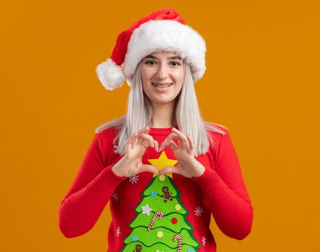 Młoda Blondynka W świątecznym Swetrze I Santa Hat Patrząc Na Kamery Z Uśmiechem Na Twarzy Robi Gest Serca Palcami Stojącymi Na Pomarańczowym Tle Darmowe Zdjęcia