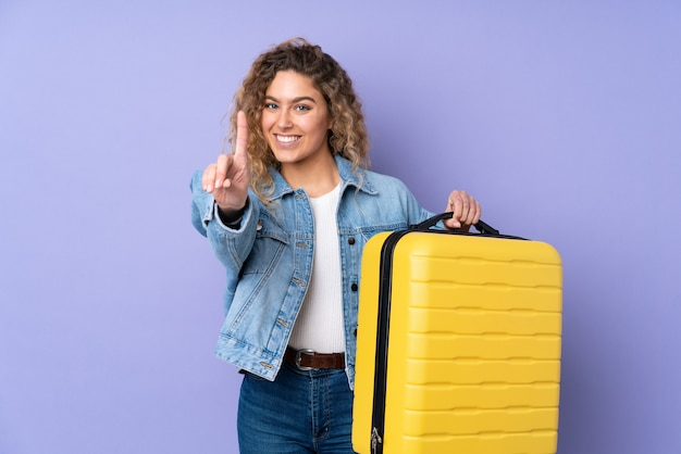 Młoda Blondynka Z Kręconymi Włosami Na Fioletowym Tle Na Wakacjach Z Walizką Podróżną I Liczy Jeden Premium Zdjęcia