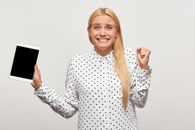Młoda Blondynka Zacisnęła Pięść Z Radości, Wygląda Na Zadowoloną Z Tabletem W Dłoni Darmowe Zdjęcia