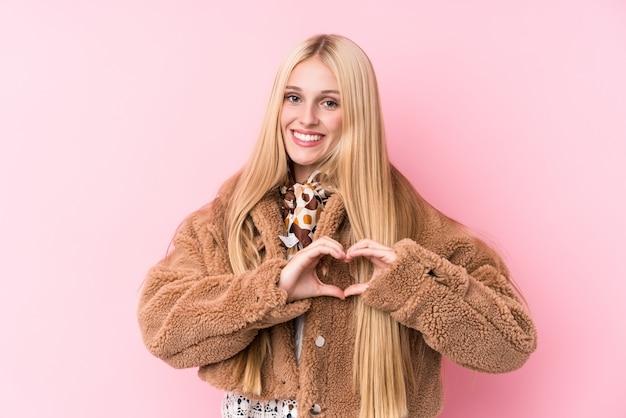 Młoda Blondynki Kobieta Jest Ubranym żakiet Przeciw Różowej ścianie Uśmiecha Się Kierowego Kształt Z Rękami I Pokazuje. Premium Zdjęcia