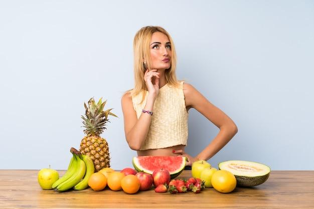 Młoda Blondynki Kobieta Myśleć Mnóstwo Pomysł Z Owoc Premium Zdjęcia