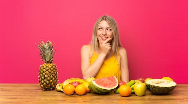 Młoda Blondynki Kobieta Myśleć Pomysł Z Dużą Ilością Owoc Premium Zdjęcia