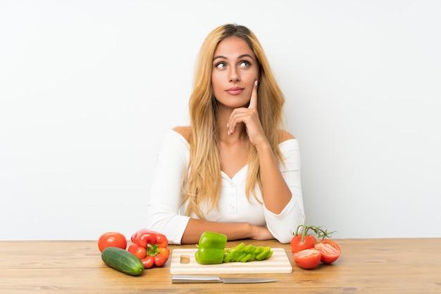 Młoda Blondynki Kobieta Myśleć Warzywa Z Stołem W Stole Premium Zdjęcia