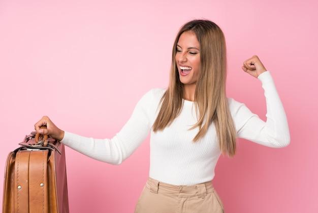 Młoda blondynki kobieta nad odosobnionymi menchiami trzyma rocznik teczkę Premium Zdjęcia