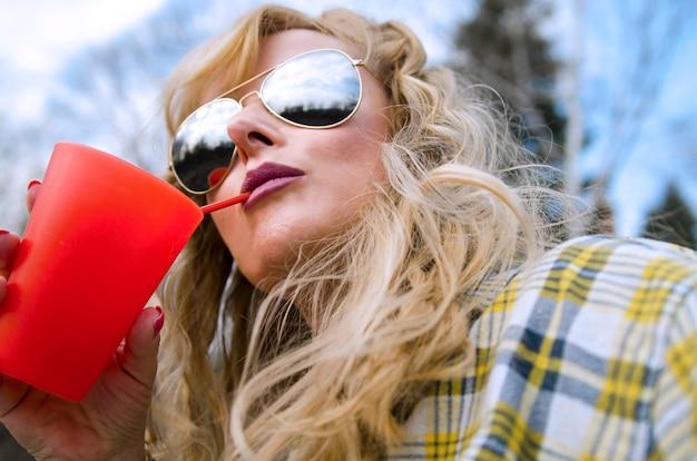 Młoda Blondynki Kobieta Pije Na Słomie Od Czerwonego Szkła Z Okularami Przeciwsłonecznymi Premium Zdjęcia