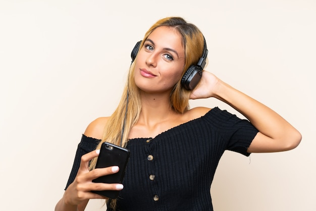 Młoda blondynki kobieta słucha muzykę z wiszącą ozdobą Premium Zdjęcia