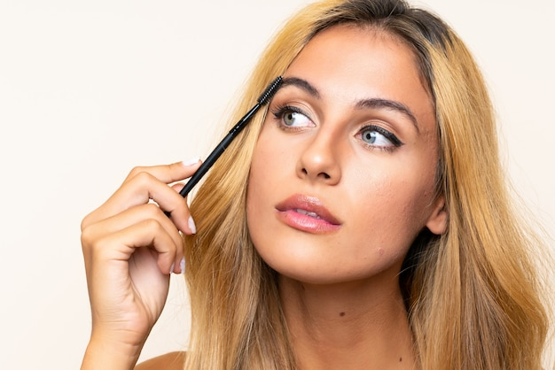 Młoda blondynki kobieta stosuje tusz do rzęs z kosmetycznym pośpiechem Premium Zdjęcia
