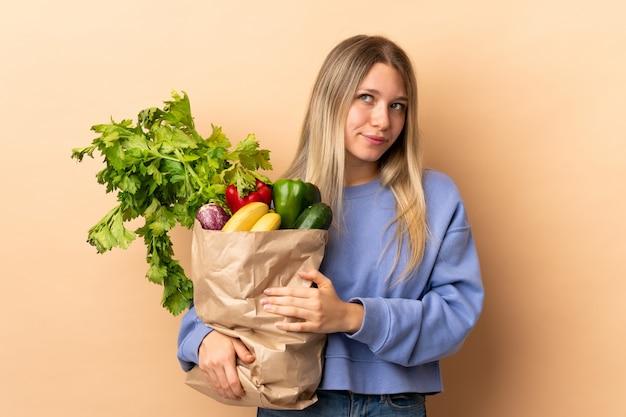 Młoda Blondynki Kobieta Trzyma Torbę Warzywa Pełno Nad Odosobnioną ścianą Myśleć Pomysł Premium Zdjęcia