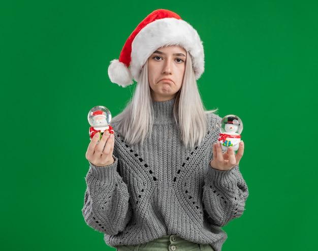 Młoda Blondynki Kobieta W Zimowym Swetrze I Czapce Mikołaja Trzymająca świąteczne Zabawki śnieżne Kule Patrząc Na Kamerę Ze Smutnym Wyrazem Wydrążającym Usta Stojąc Na Zielonym Tle Darmowe Zdjęcia