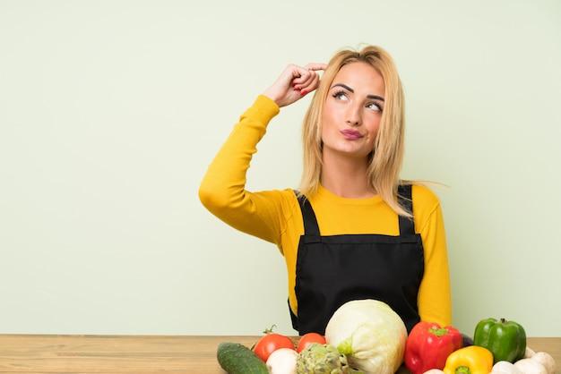 Młoda Blondynki Kobieta Z Dużą Ilością Warzyw Ma Wątpliwości I Z Zmieszanym Wyrazem Twarzy Premium Zdjęcia