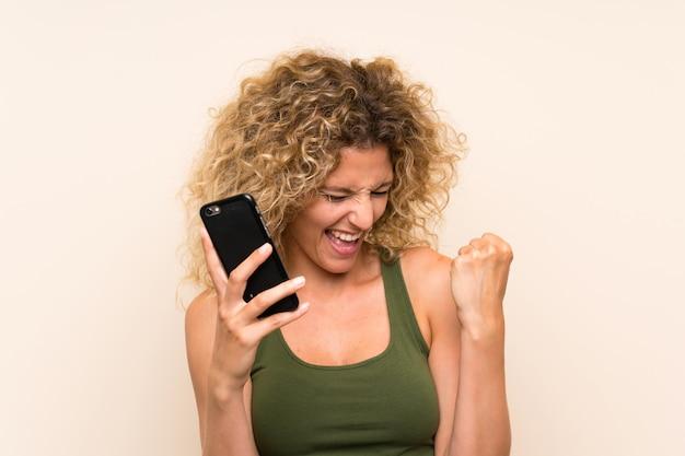 Młoda blondynki kobieta z kędzierzawym włosy używać telefon komórkowego świętuje zwycięstwo Premium Zdjęcia