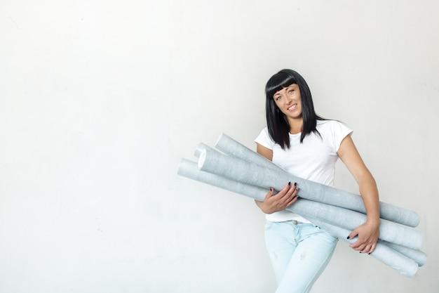Młoda Brunetka Kobieta Trzyma Rolki Tapety W Dłoniach Na Tle Białej ściany Premium Zdjęcia