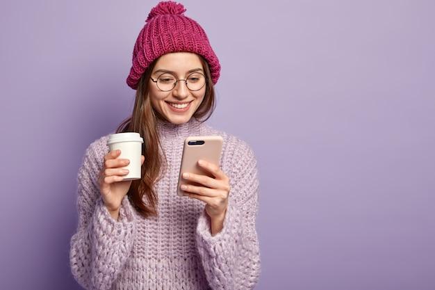 Młoda Brunetka Kobieta Ubrana W Fioletowy Sweter I Trzymając Filiżankę Kawy Darmowe Zdjęcia