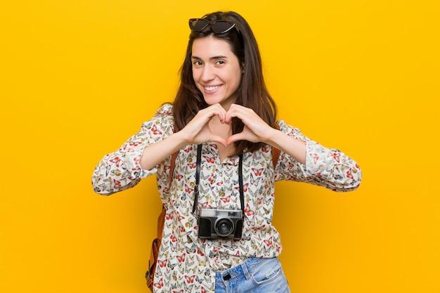 Młoda Brunetka Podróżnika Kobieta Uśmiecha Się Kierowego Kształt I Pokazuje Z Rękami. Premium Zdjęcia