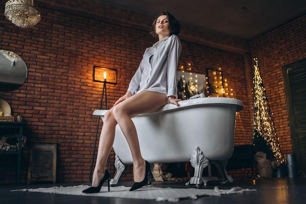 Młoda Brunetka Siedząca Na Brzegu Wanny Premium Zdjęcia