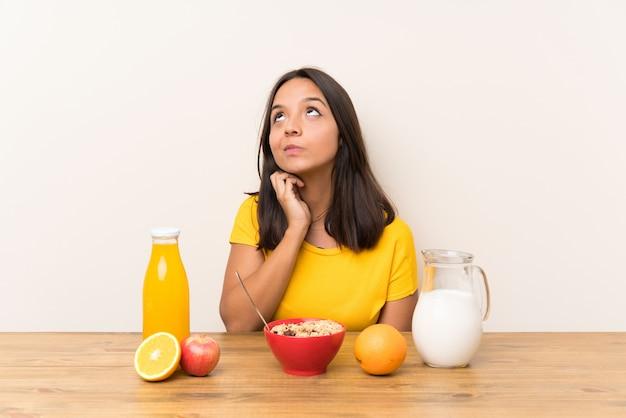 Młoda Brunetki Dziewczyna Ma śniadania Mleko Myśleć Pomysł Premium Zdjęcia