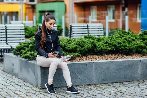 Młoda brunetki kobieta jest relaksująca po joggingu i trzyma wodę. Premium Zdjęcia